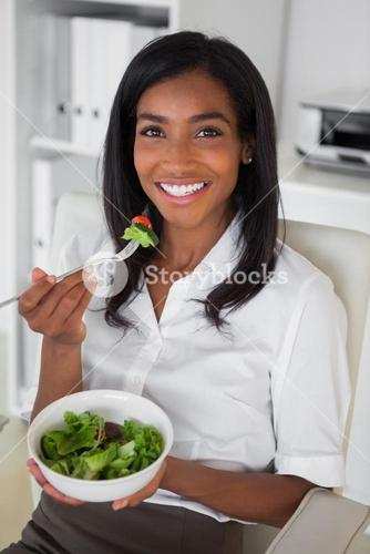 Casual pretty businesswoman eating a salad at her desk