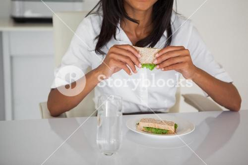 Pretty businesswoman eating a sandwich at her desk