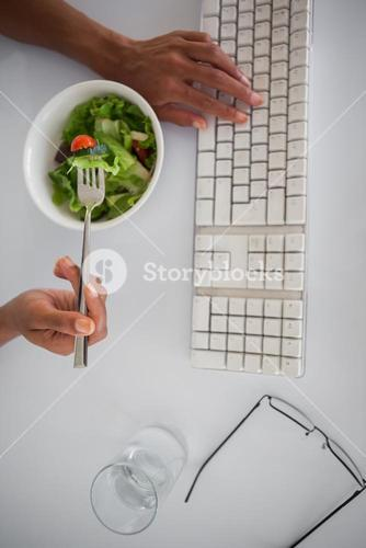 Businesswoman eating a salad at her desk