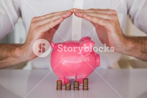 Casual businessman sheltering piggy bank and coins