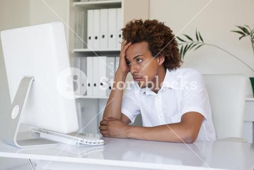 Casual stressed businessman looking at his computer