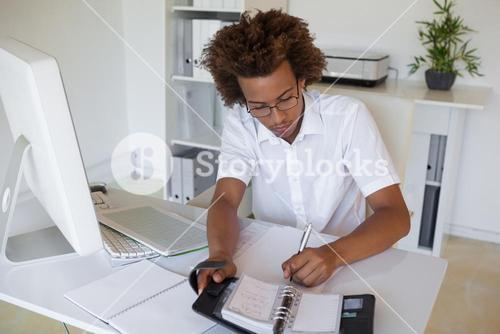 Casual young businessman organizing his schedule at his desk