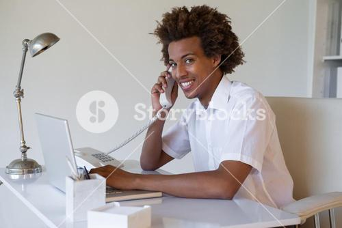 Focused casual businessman on the phone using laptop at desk