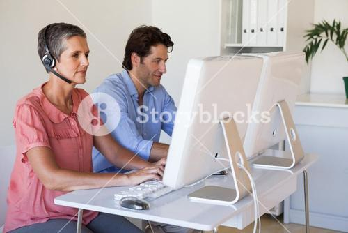 Casual business team working at desk using computers with woman using headset