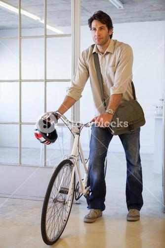 Casual businessman pushing his bike