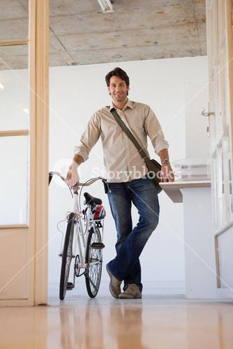 Casual businessman standing with his bike smiling at camera