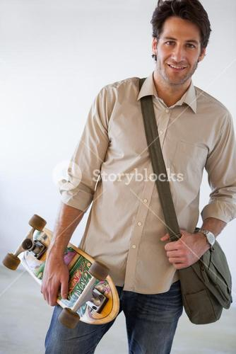 Casual businessman standing with his skateboard smiling at camera