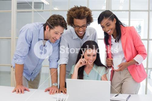 Coworkers interacting with laptop computer