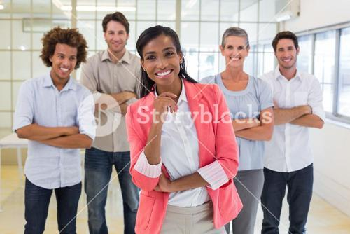 Well dressed workers with arms folded smiling at camera