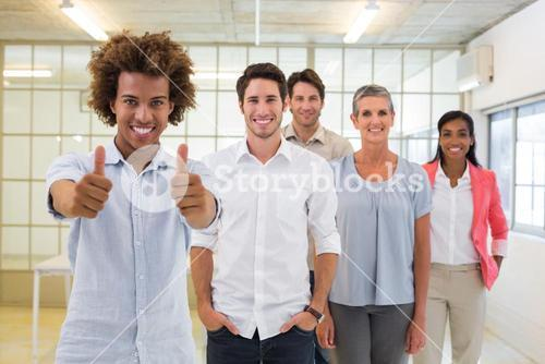 Group of business people giving thumbs up to camera