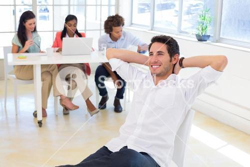Businessman relaxing with colleagues in background