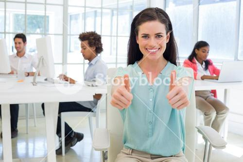 Attractive worker gives two thumbs up to camera