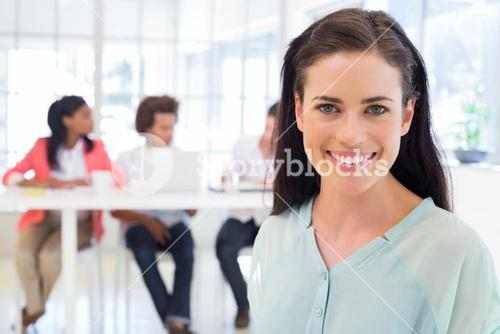 Smiling businesswoman with coworkers in background