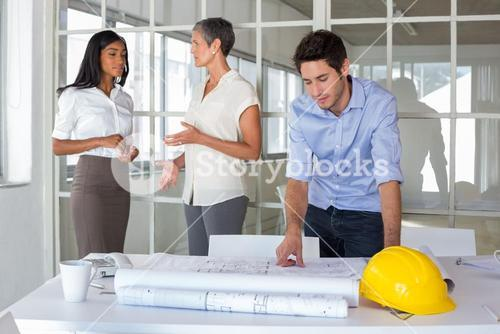 Workers talking and looking over plans