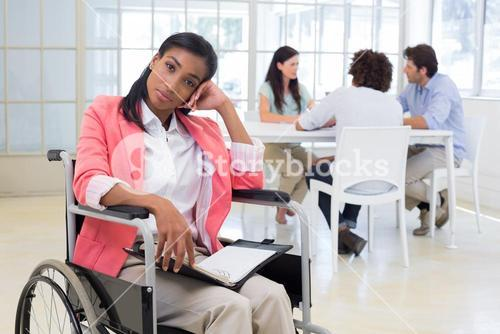 Woman with disability frowning with coworkers are in background