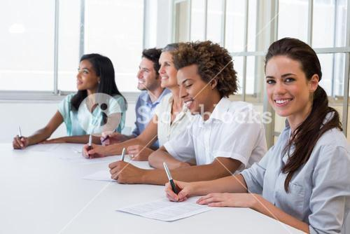 Worker at board meeting smiles to camera