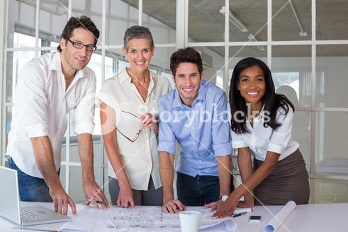 Team of architects going over blueprints smiling at camera