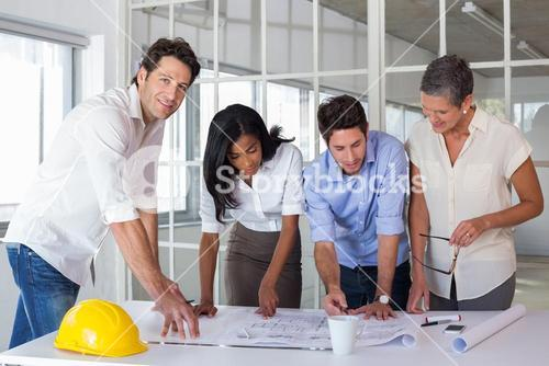 Team of architects going over blueprints with one smiling at camera