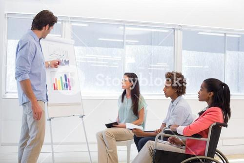 Attractive businessman making a presentation to his fellow coworkers
