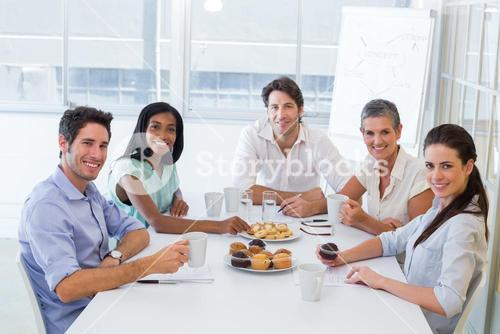 Work colleagues having hot beverages and muffins and smiling at the camera