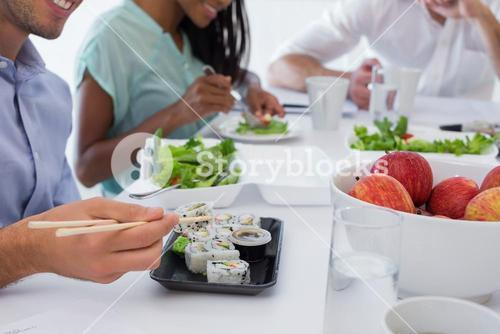 Business people enjoying sushi and salad for lunch