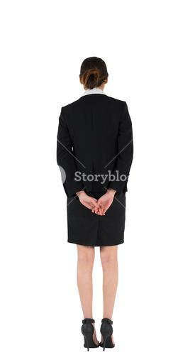 Businesswoman in suit standing with hands behind back