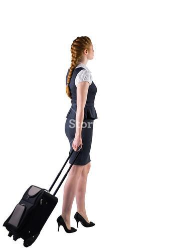 Redhead businesswoman pulling her suitcase