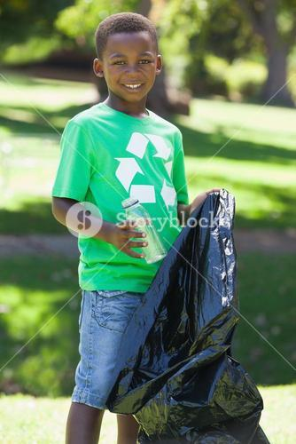 Young boy in recycling tshirt picking up trash