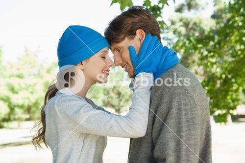 Cute couple standing in the park in hats and scarves