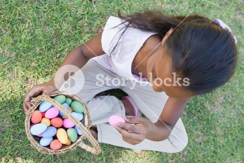 Little girl sitting on grass counting easter eggs