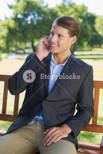 Casual businessman talking on phone on park bench