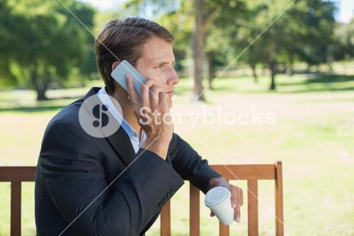 Casual businessman talking on phone on park bench with coffee
