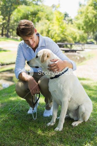Handsome man with his labrador in the park