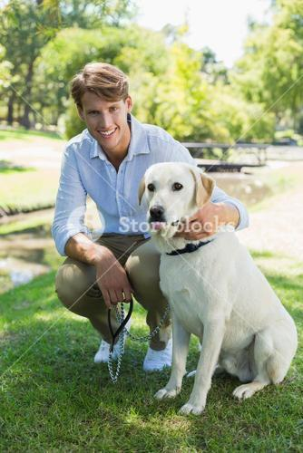 Handsome man with his labrador in the park smiling at camera