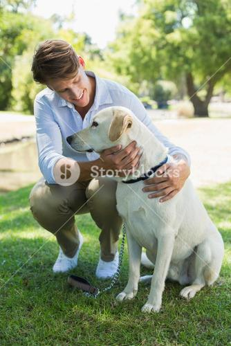 Handsome smiling man with his labrador in the park
