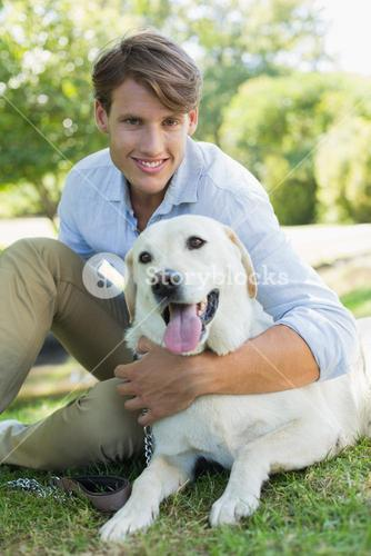 Handsome smiling man with his labrador sitting in the park