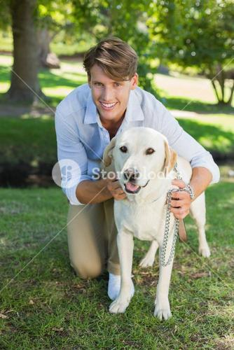 Handsome smiling man posing with his labrador in the park