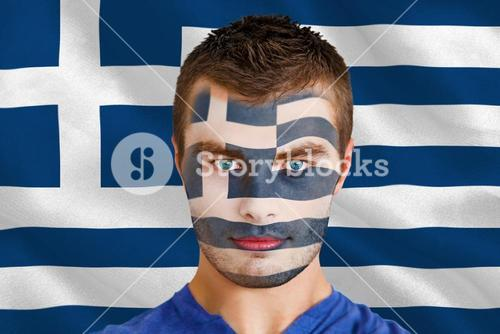 Serious young greece fan with facepaint