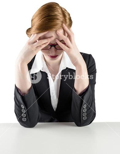 Redhead businesswoman with head in hands