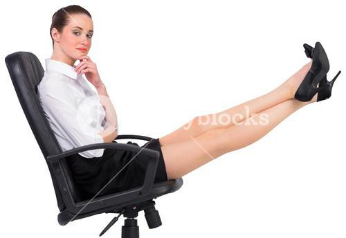 Businesswoman sitting on swivel chair with feet up