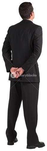 Businessman standing and looking with hands behind back