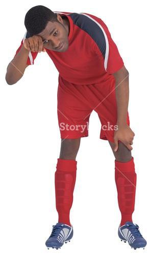 Football player in red catching his breath