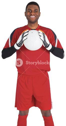 Goalkeeper in red holding the ball