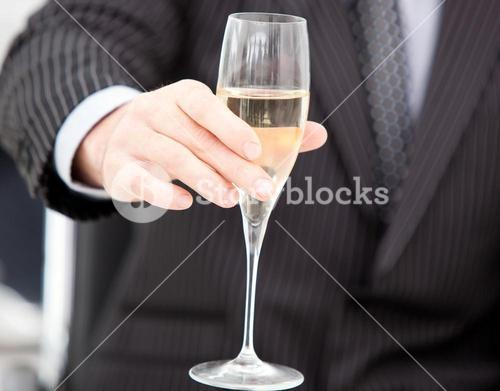 Close up of a businessman holding a glass of champaign