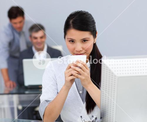 Assertive Businesswoman drinking a coffee at her desk