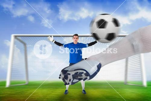 Football player striking ball at goalkeeper