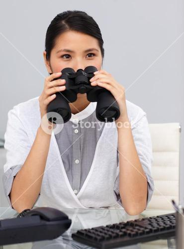 Serious young Businesswoman using binoculars