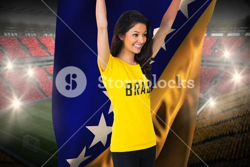 Excited football fan in brasil tshirt holding bosnia flag