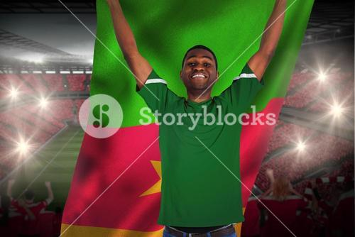 Cheering football fan in green jersey holding cameroon flag