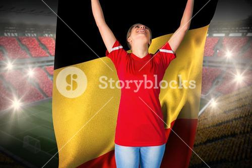 Cheering football fan in red holding belgium flag